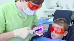 Dentist holds jaw and uses light for harden filling near boy Stock Footage