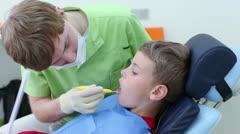 Dentist checks teeth of boy by dental mirror in surgery Stock Footage