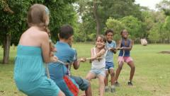 Happy school children playing tug of war in park - stock footage