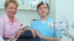 Nurse and doctor sit and then take drilling machine Stock Footage