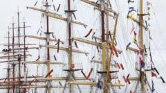 Masts of sailing ships stand with collected sails and flags Stock Footage