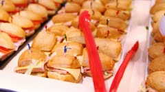 Small hot sandwiches stand on white tray on table in dishes Stock Footage