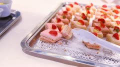 Small cakes stands on white tray on table in dishes Stock Footage