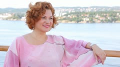 Red-haired woman stands on ship deck in sunny weather Stock Footage