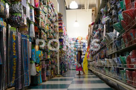 Stock photo of Pretty Little Girl Shopping In A Dollar Store Party Section