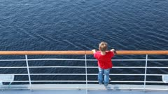 Boy looks at water standing on ship deck in afternoon Stock Footage
