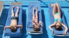 Mother, daughter and son sunbathe in chaise lounges on deck ship Stock Footage