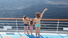 Mother, daughter and son stands waving hands on board ship Stock Footage