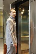 Businessman about to enter elevator Stock Photos