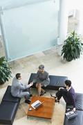 Three businesspeople meeting in lobby Stock Photos
