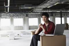 Young woman sitting in construction site Stock Photos