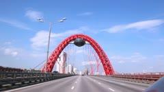 Cars go on Zhivopisny Bridge against blue cloudy sky Stock Footage