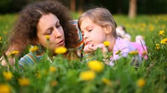 Mother and daughter talk lying on lawn in sunny weather Stock Footage