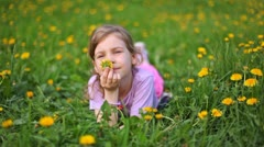 Girl smells dandelion on green lawn covered with flowers Stock Footage