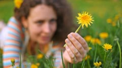 Young beautiful woman lies on lawn with dandelion in hand Stock Footage