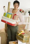 Portrait of woman holding gifts and wrapping paper Stock Photos
