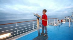 Boy in red tee-shirt looks in field-glass on ship deck Stock Footage