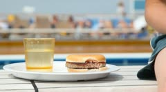 Hamburger on plate near glass with juice and boy nearby Stock Footage