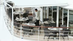 Serving in white vacuums floor among tables on open deck of ship Stock Footage