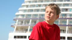 Boy squints from sun against decks of big ship close up Stock Footage