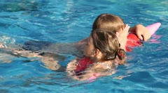 Brother and sister swim on inflatable toy-pencil in pool Stock Footage
