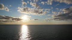 Line of horizon dividing sea and sky with sun and clouds Stock Footage