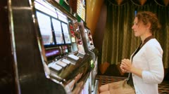 Woman plays with slot machine and discontentedly poses face Stock Footage