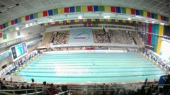 Audience looks competitions on swimming in Sports complex Stock Footage