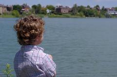Young Boy Overlooking Lake - stock photo