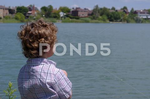 Stock photo of Young Boy Overlooking Lake