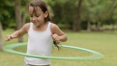 Happy young girl playing with hula-hoop in park Stock Footage