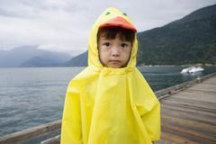 Portrait of boy in ducky raincoat - stock photo