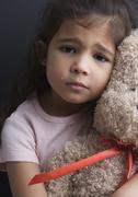 Portrait of tyttö itkee ja halaa nalle Kuvituskuvat