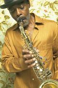 Keski-ikäinen mies pelissä saksofoni Kuvituskuvat