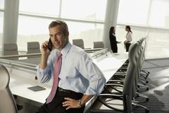 Businessman talking on cell phone in conference room Stock Photos