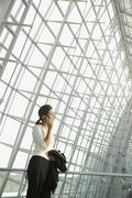 Businesswoman talking on cell phone in airport - stock photo