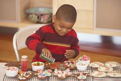 Young boy making gingerbread men - stock photo
