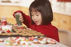 Little girl decorating gingerbread men Stock Photos