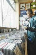 Teenage boy listening to headphones in a music store Stock Photos