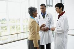 Doctors talking to businesswoman Stock Photos