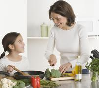 Mother and daughter cooking together - stock photo