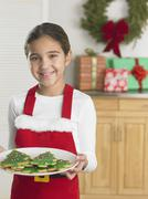 Young girl in a Santa apron holding a plate of Christmas cookies - stock photo