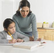 Mother helping her daughter with her homework Stock Photos
