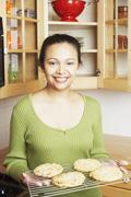 Young woman holding a rack of baked goods Stock Photos