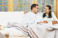 Couple sitting on the couch under a blanket together - stock photo