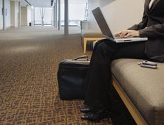 Businesswoman using a laptop in foyer Stock Photos