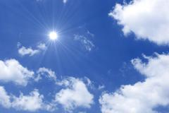 Blue sky with sun and beautiful clouds Stock Photos