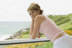 Young woman leaning on railing Stock Photos