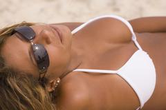 Hispanic woman in bathing suit tanning Stock Photos