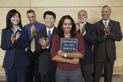 Businesswoman holding Employee of the Month plaque with co-workers applauding Stock Photos